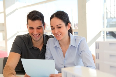 11852409 - happy young couple signing property purchase contract